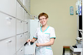 beautiful girl pharmacist at the pharmacy, the pharmacist sells drugs. Young woman doctor working in pharmacy happy