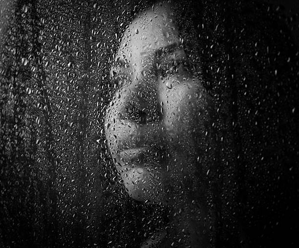 Beautiful girl A beautiful girl in a white t-shirt, on a black background behind the glass. wet clothing women t shirt stock pictures, royalty-free photos & images