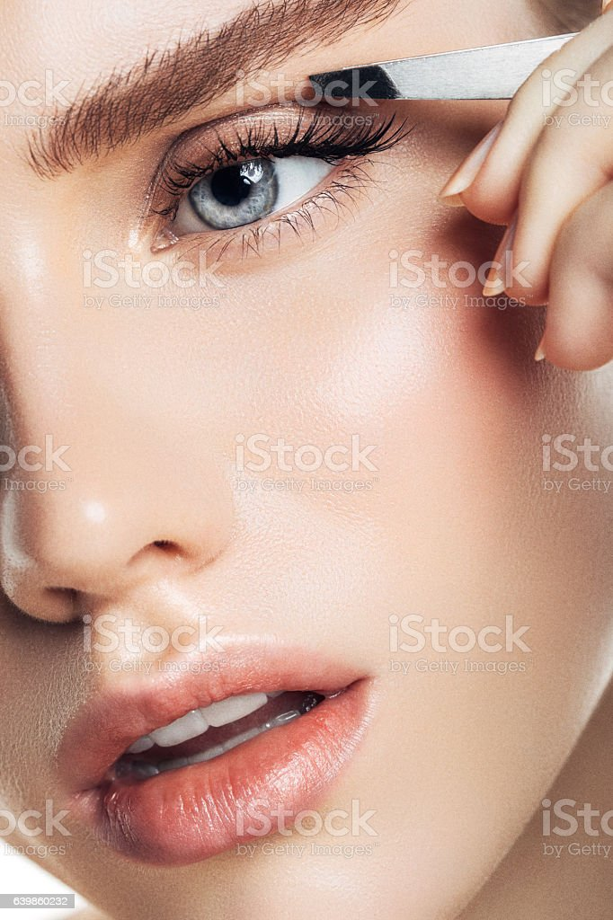 Beautiful girl plucks eyebrows stock photo