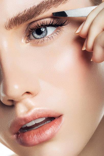Beautiful girl plucks eyebrows stock photo