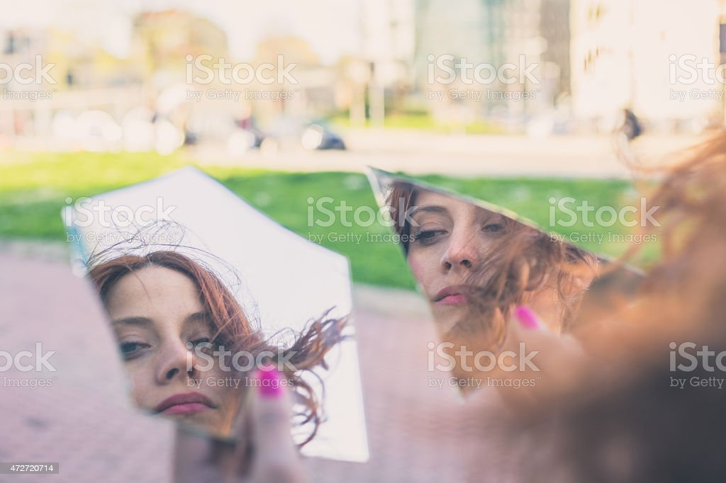 Beautiful girl posing in the city streets Beautiful redhead girl with long hair and blue eyes looking at herself in a broken mirrorBeautiful redhead girl with long hair and blue eyes posing in an urban context 2015 Stock Photo