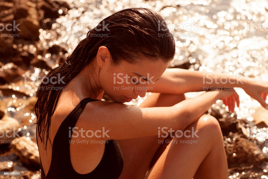 Beautiful girl posing on the rocks and stones and the seaside. stock photo