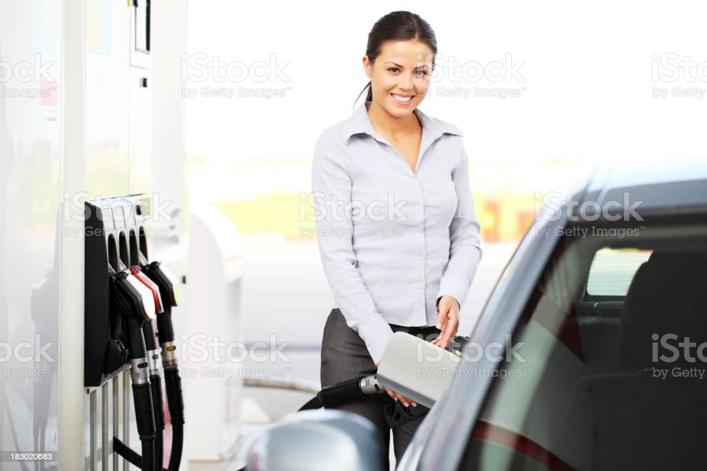 Beautiful girl poured fuel into the tank cars to pumps. stock photo