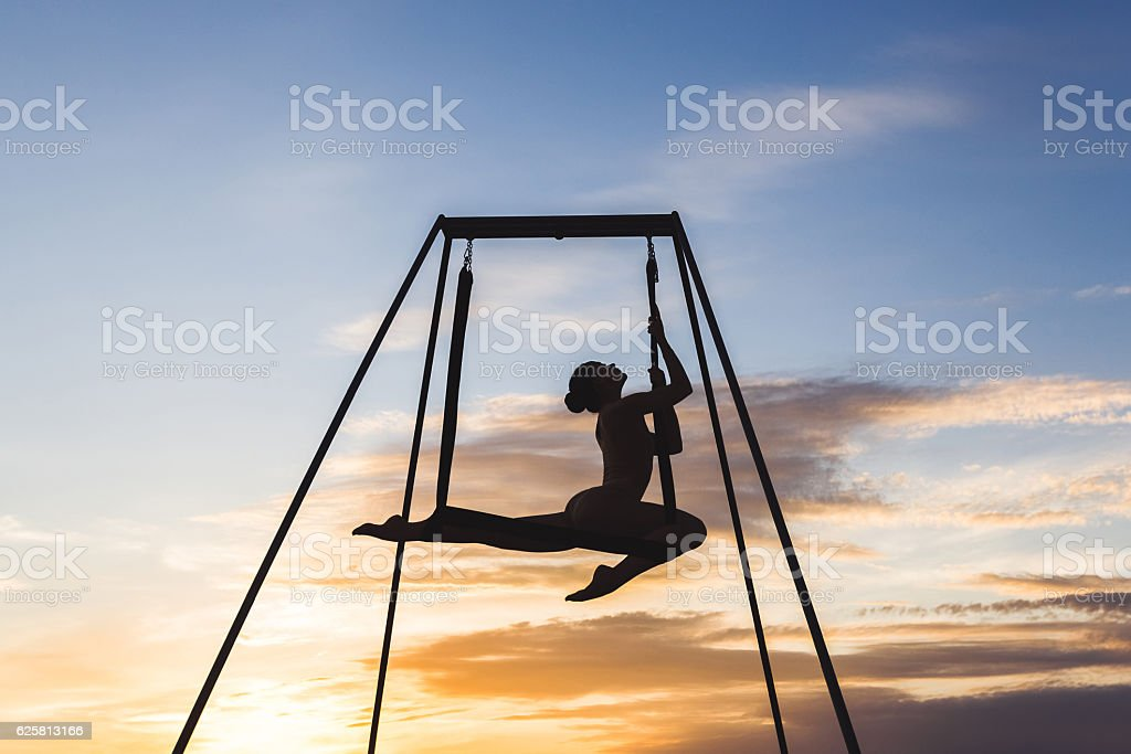 Beautiful girl practicing fly-yoga poses in a hammock outdoor at stock photo