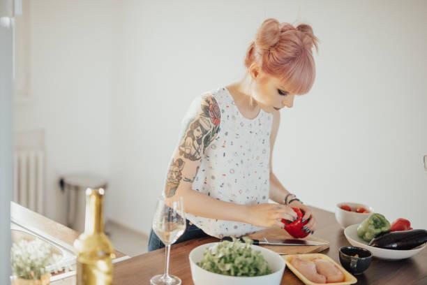 schöne mädchen vorbereitung abendessen - essen tattoos stock-fotos und bilder