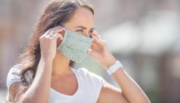 Schöne Mädchen legt Riemen ihrer Polka Dot Gesichtsmaske über ihre Ohren an einem sonnigen Tag. – Foto