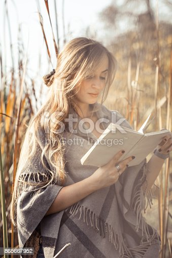 862602714istockphoto beautiful girl reading a book in autumn forest 865667952