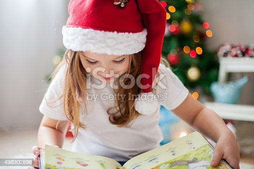 istock Beautiful girl, reading a book in front of Christmas tree 498302898