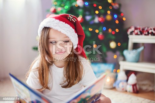 istock Beautiful girl, reading a book in front of Christmas tree 498889114