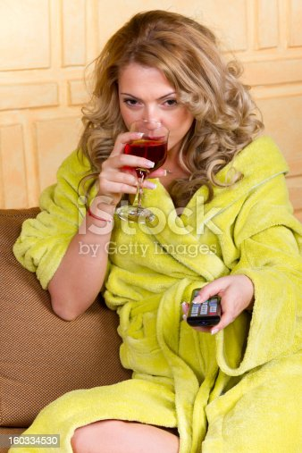 Beautiful blonde girl relaxes on the sofa drinking a glass of red wine and change the TV channels at home using remote control ,  She wears a bathrobe yellowish green color. On the background is yellow wall with aged pattern .