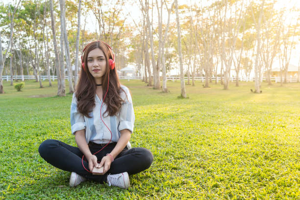 Hermosa chica relajante y escuchar música en los auriculares en el parque en el fondo borroso. Mujer en los auriculares. - foto de stock