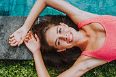 Beautiful girl relaxing outdoor in her garden with swimming pool. Summer concept about lifestyle,beauty, vacations and real estates