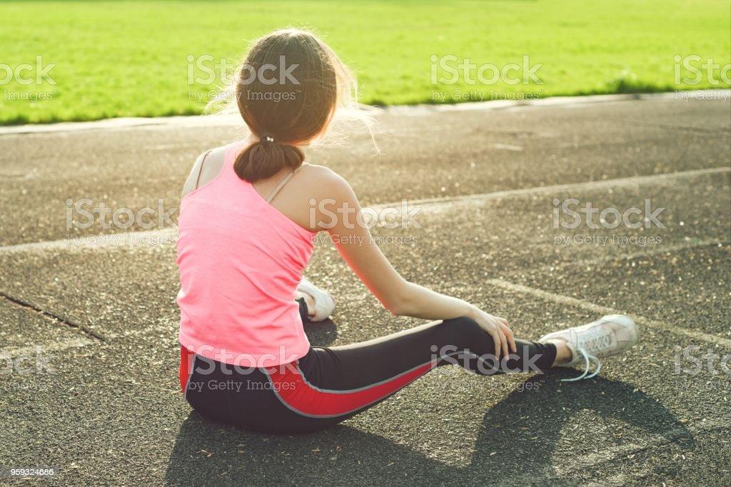 Beautiful girl resting after workout at stadium stock photo