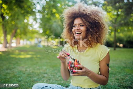 Portrait of a beautiful Afro girl sitting at the park, eating fruits and enjoying.