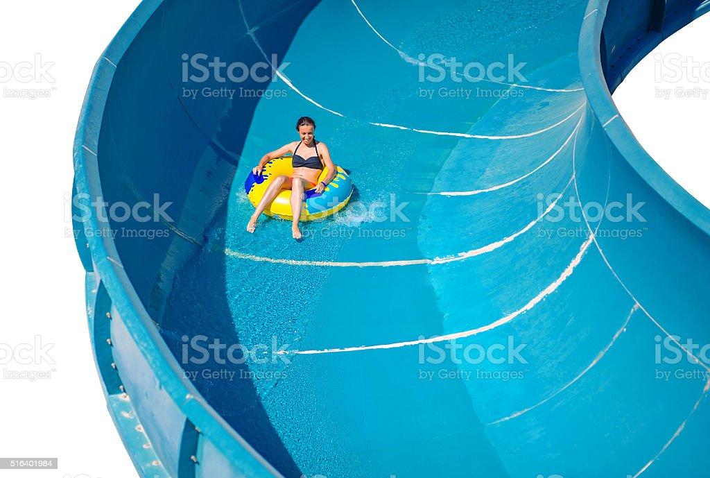 Beautiful girl riding a water slide stock photo