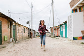 Beautiful girl running in shanty town. Poor infant concept
