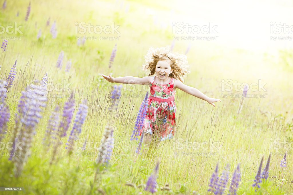 Beautiful girl running through field with flower. royalty-free stock photo