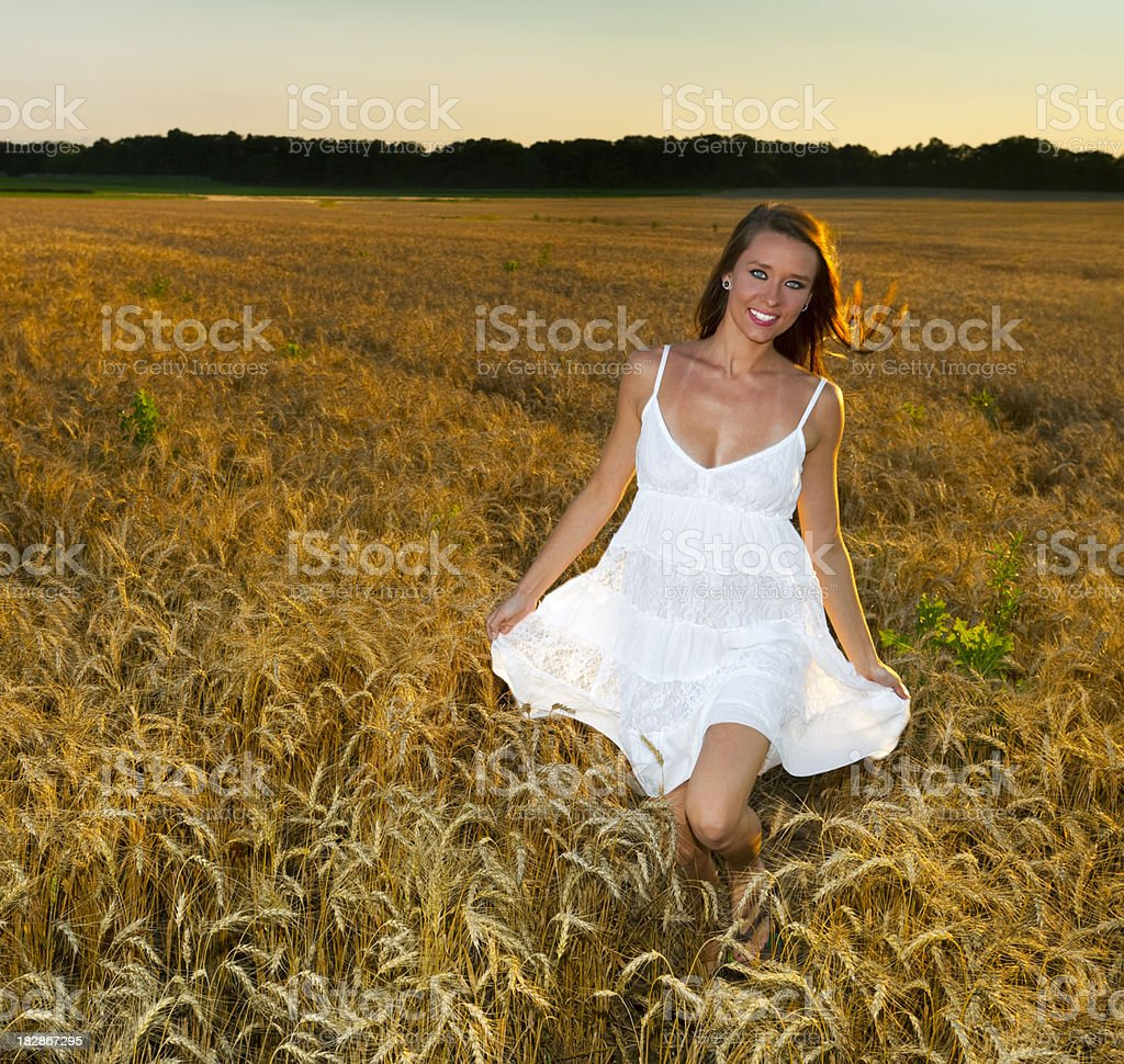 Beautiful Girl Running Through Wheat Field at Sunset royalty-free stock photo