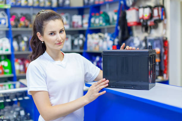 Beautiful girl saleswoman offers the best battery for car in an auto parts store stock photo
