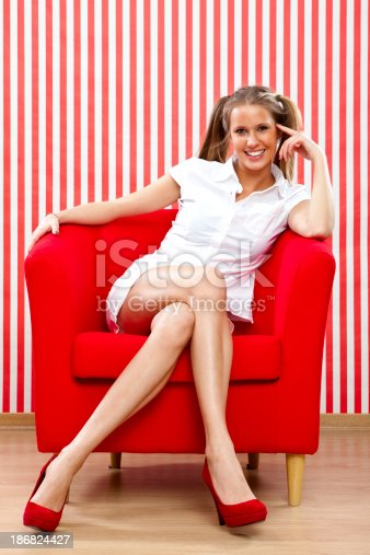 istock Beautiful girl sat on armchair red portrait 186824427