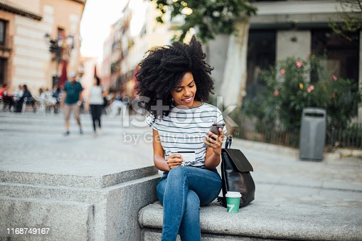 Beautiful, young African - American woman sitting on the street and shopping online.