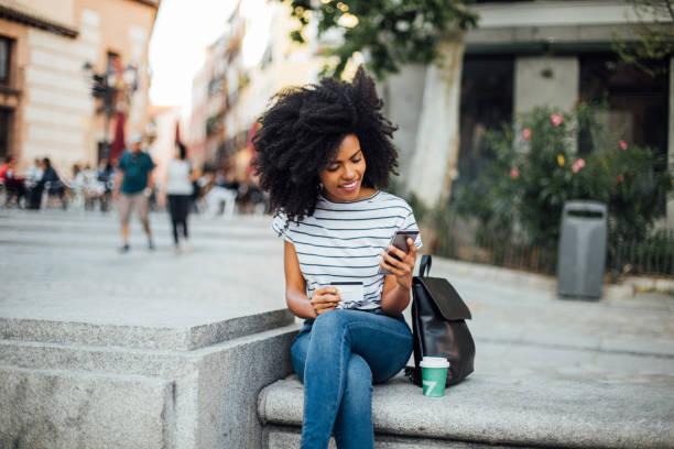 schöne mädchen online-shopping auf der straße - konsum stock-fotos und bilder