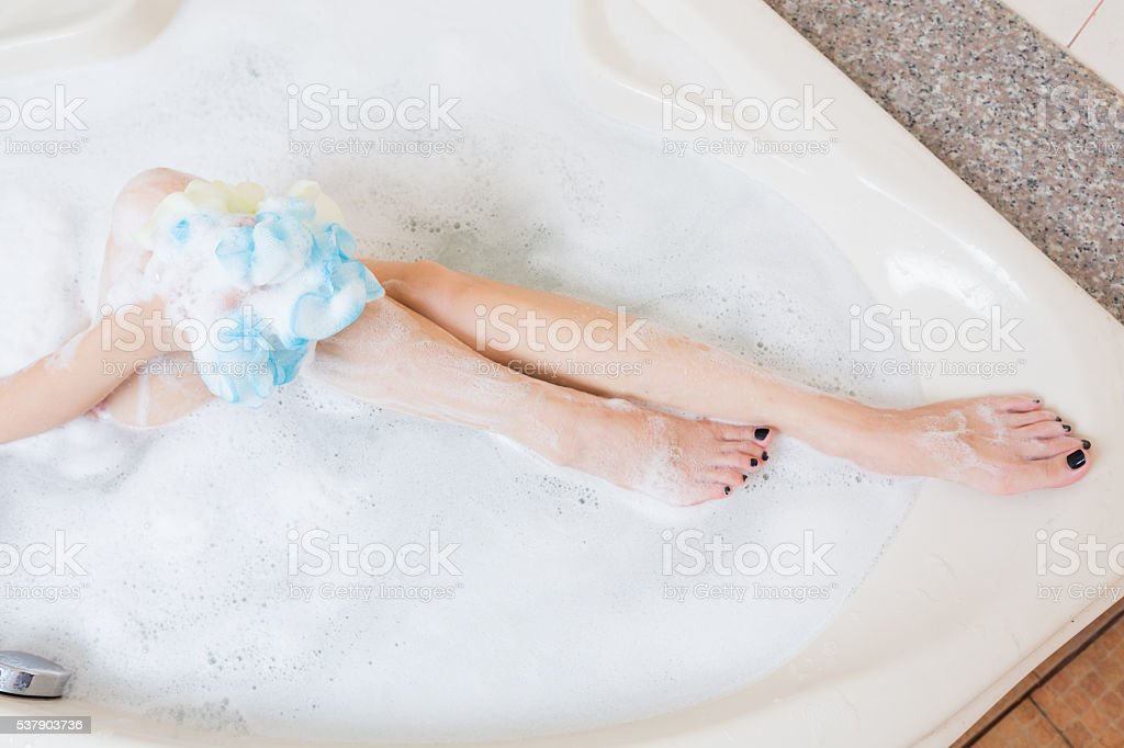 Beautiful girl showering and washing legs in bathtub. stock photo