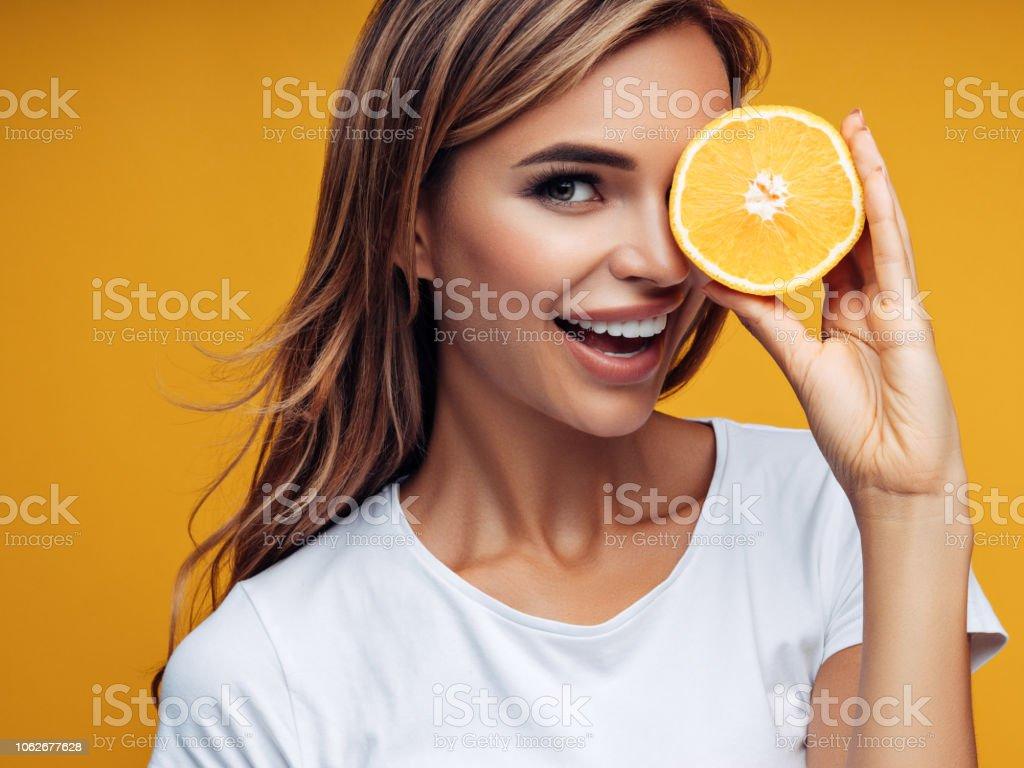 Beautiful girl showing two halves of lemon stock photo