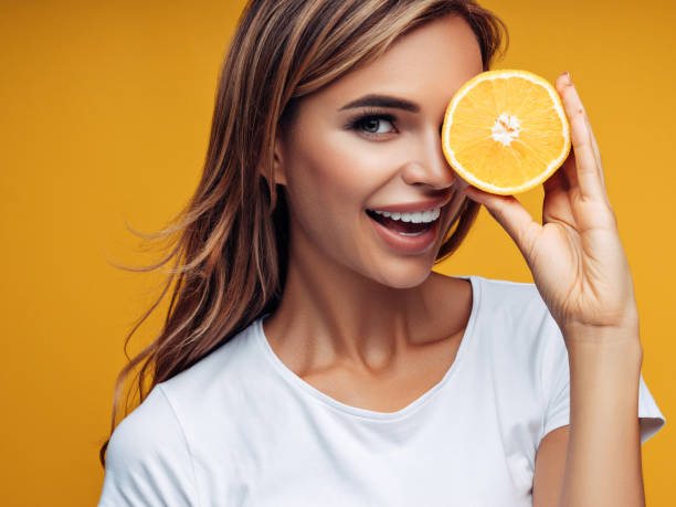 Beautiful girl showing two halves of lemon stock photo