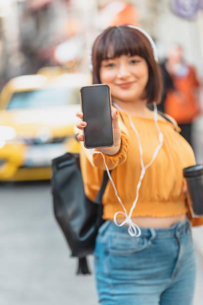 Cтоковое фото Beautiful girl shows blank screen smartphone