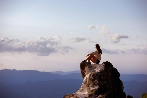 아름다운 소녀 앉아 큰 바위 에 일몰 - mountain top 뉴스 사진 이미지