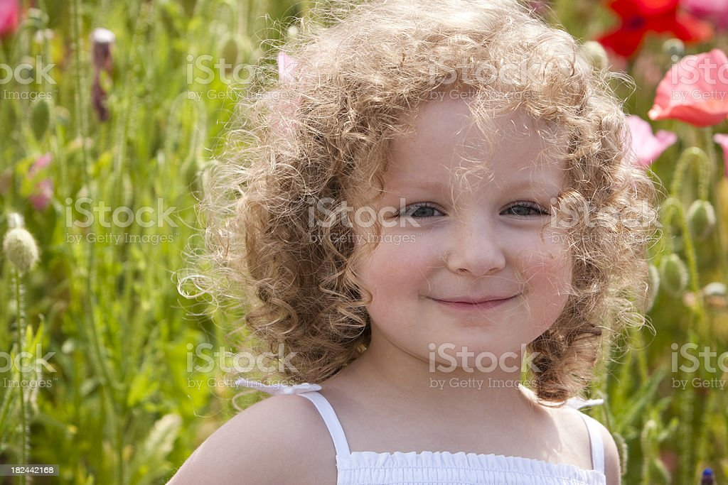 Beautiful girl sits in poppy field royalty-free stock photo