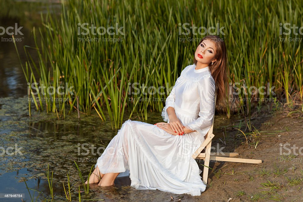 Beautiful girl sits on shore of the lake. stock photo