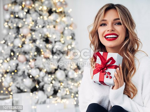 Beautiful girl sitting in a cozy atmosphere near the Christmas tree