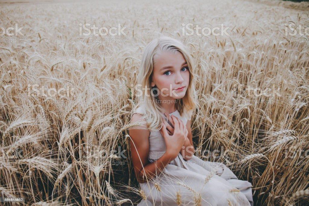 Beautiful girl sitting in a wheat field. stock photo