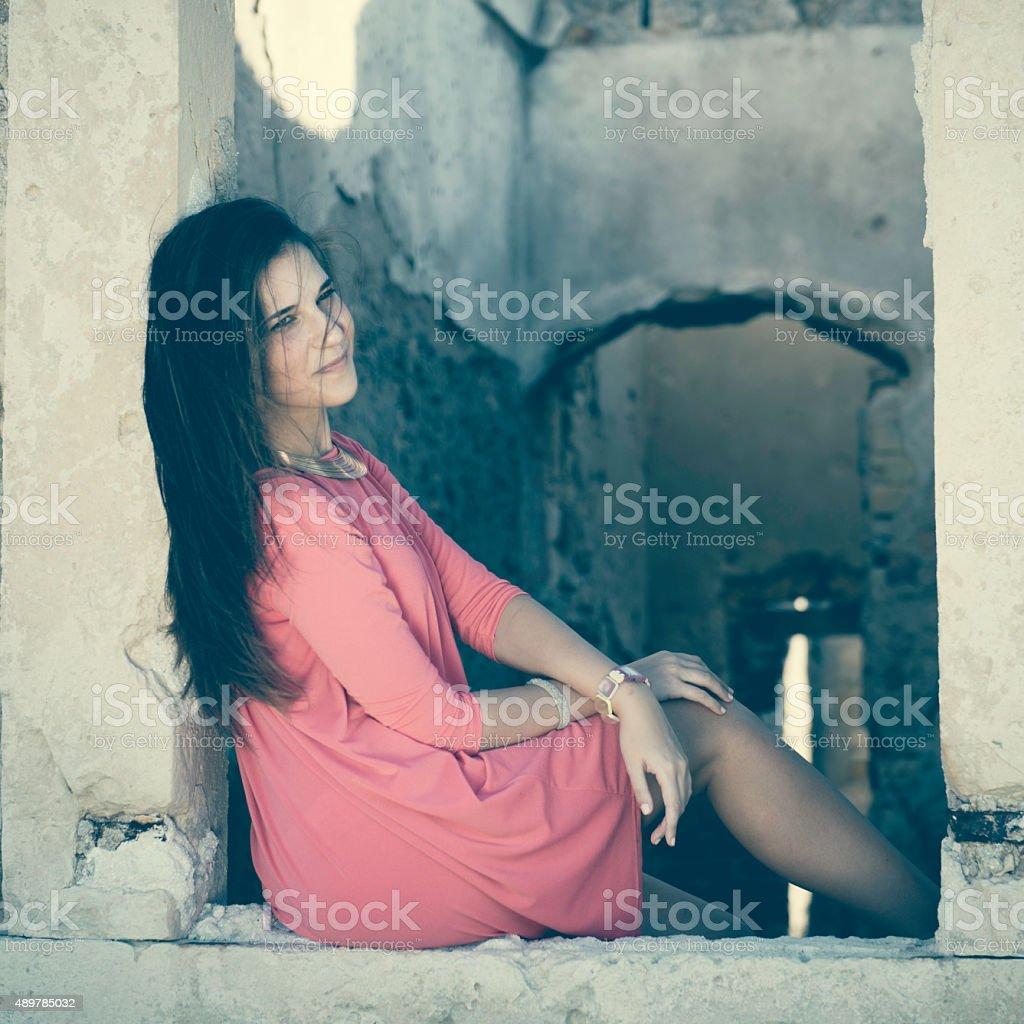 Beautiful Girl Sitting in a Window of a Ruin stock photo