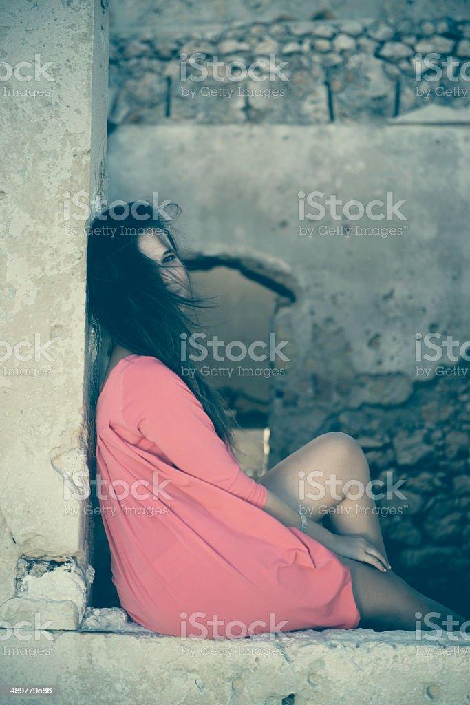 Beautiful Girl Sitting in a Window of an Old Ruin stock photo