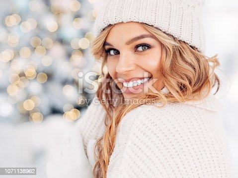 istock Beautiful girl sitting near New Year tree 1071138962