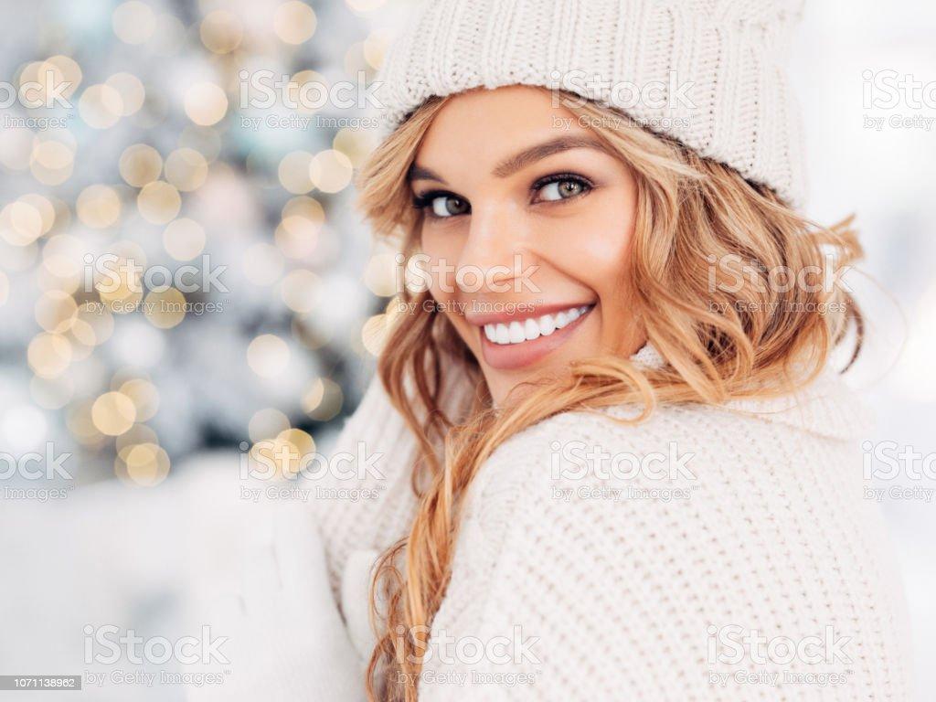 Beautiful girl sitting near New Year tree stock photo