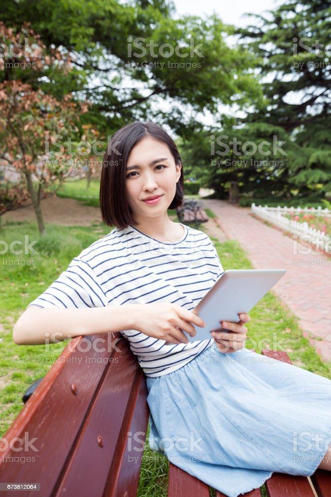 Belle fille assise sur un banc et à l'aide de tablette numérique photo libre de droits