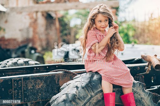 istock Beautiful girl sitting on an old tractor in the farm 859371978