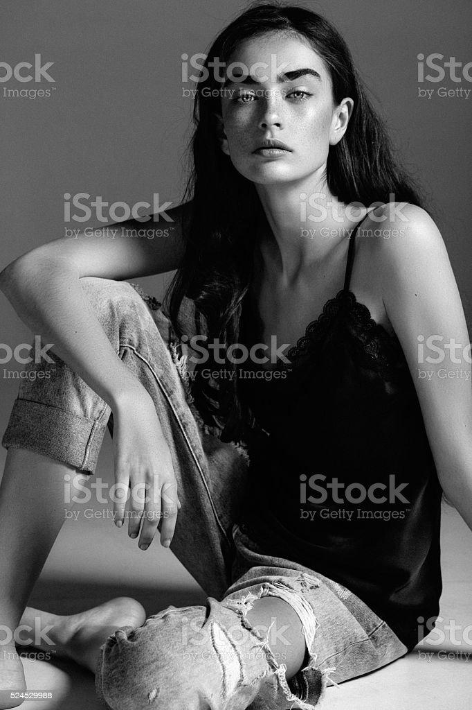 Красивая сидящая девочка на полу в студия стоковое фото
