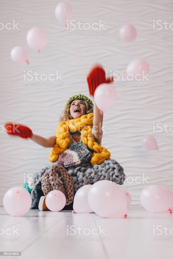 Beautiful girl sitting on the floor with knitted clothing stock photo