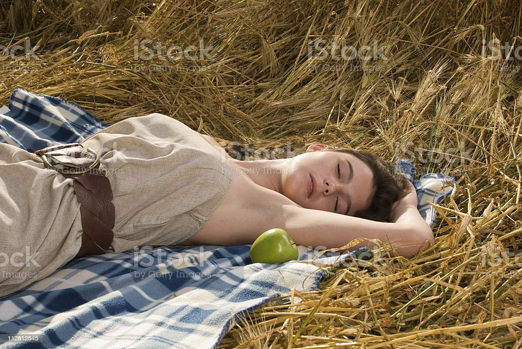 Beautiful girl sleep on picnic in wheat field with apple royalty-free stock photo