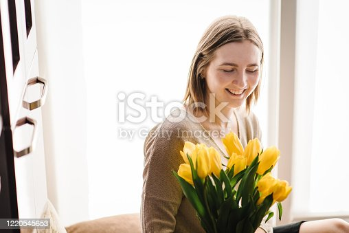 Beautiful girl smiling and holding a bouquet of tulip flowers on a light background. Surprise at the 8 march, International Women's Day. Spring flower bouquet. Happy model smelling flowers.