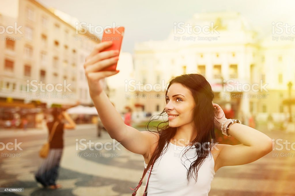 Beautiful girl smiling and taking selfie on the square stock photo