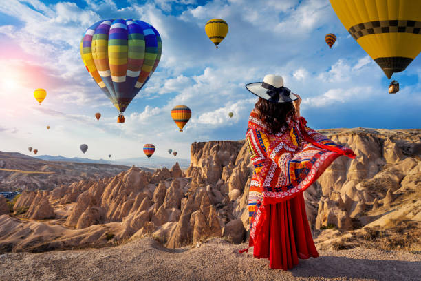 Beautiful girl standing and looking to hot air balloons in Cappadocia, Turkey. stock photo