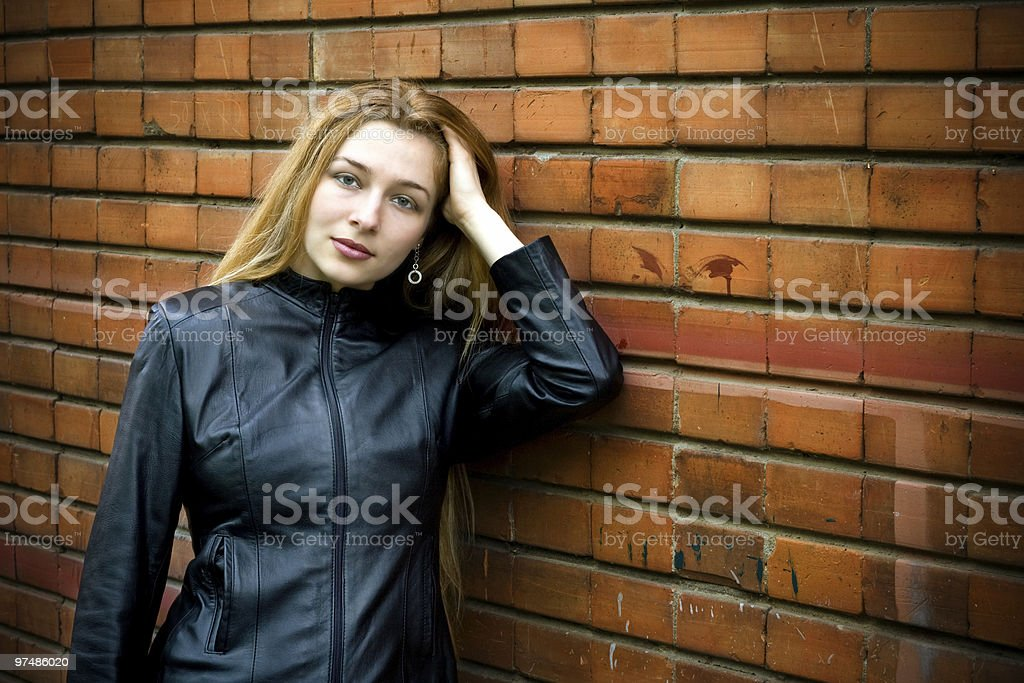 Beautiful girl standing in front of old brick wall royalty-free stock photo