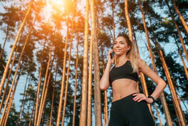 schönes mädchen steht im sommerwald park. anrufe glücklich lächelnd. in sportbekleidung joggen am morgen. freiraum für text. camping ist ein sport. - wortarten bestimmen übungen stock-fotos und bilder
