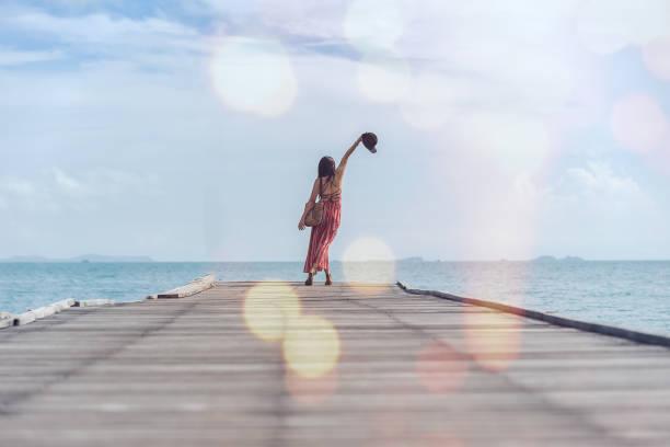 schöne mädchen stehen auf einer brücke bei sonnenuntergang - meerjungfrau kleid stock-fotos und bilder